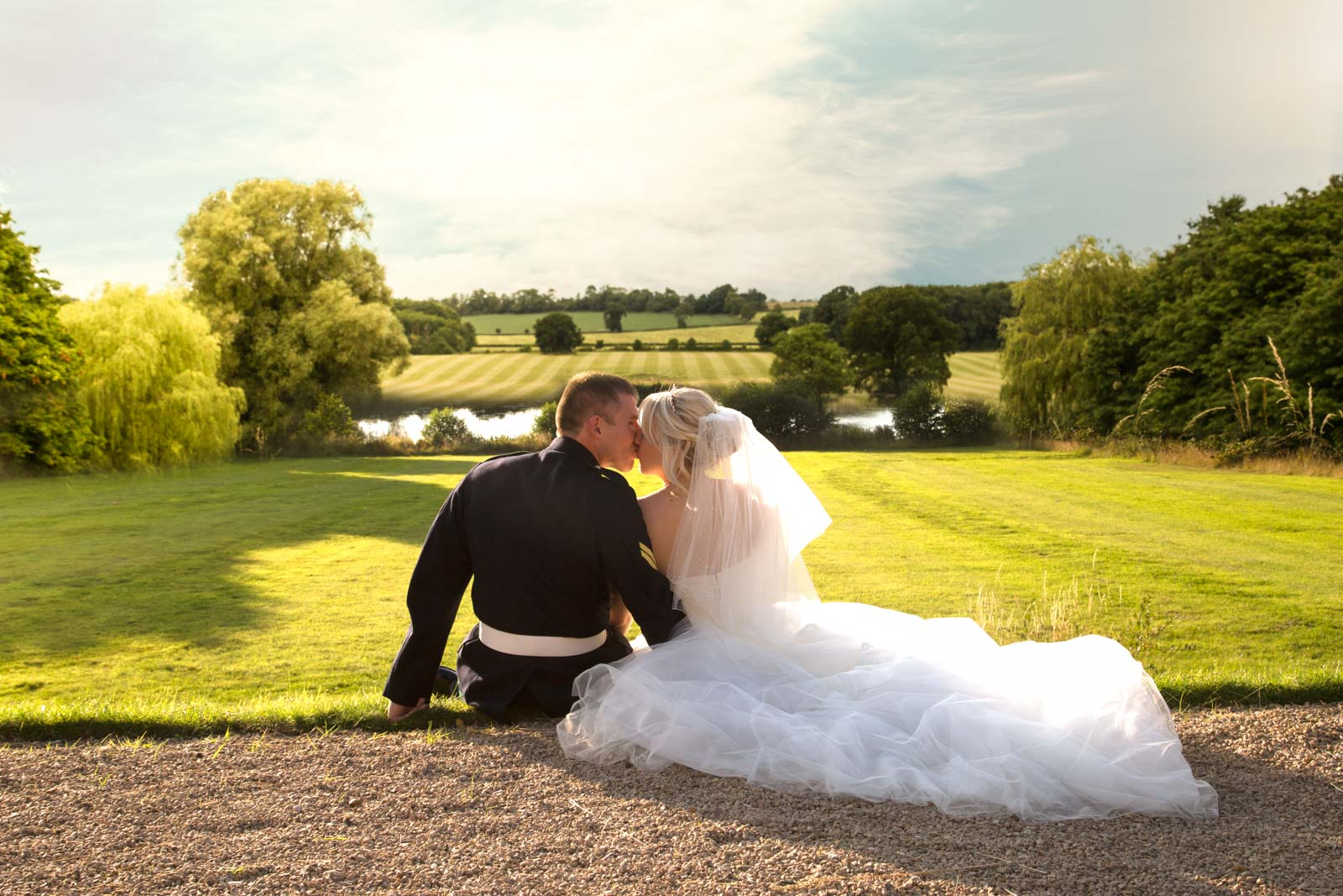 Beautiful photo of the bride and groom kissing on the lawn at Kelmarsh Hall Wedding Photography