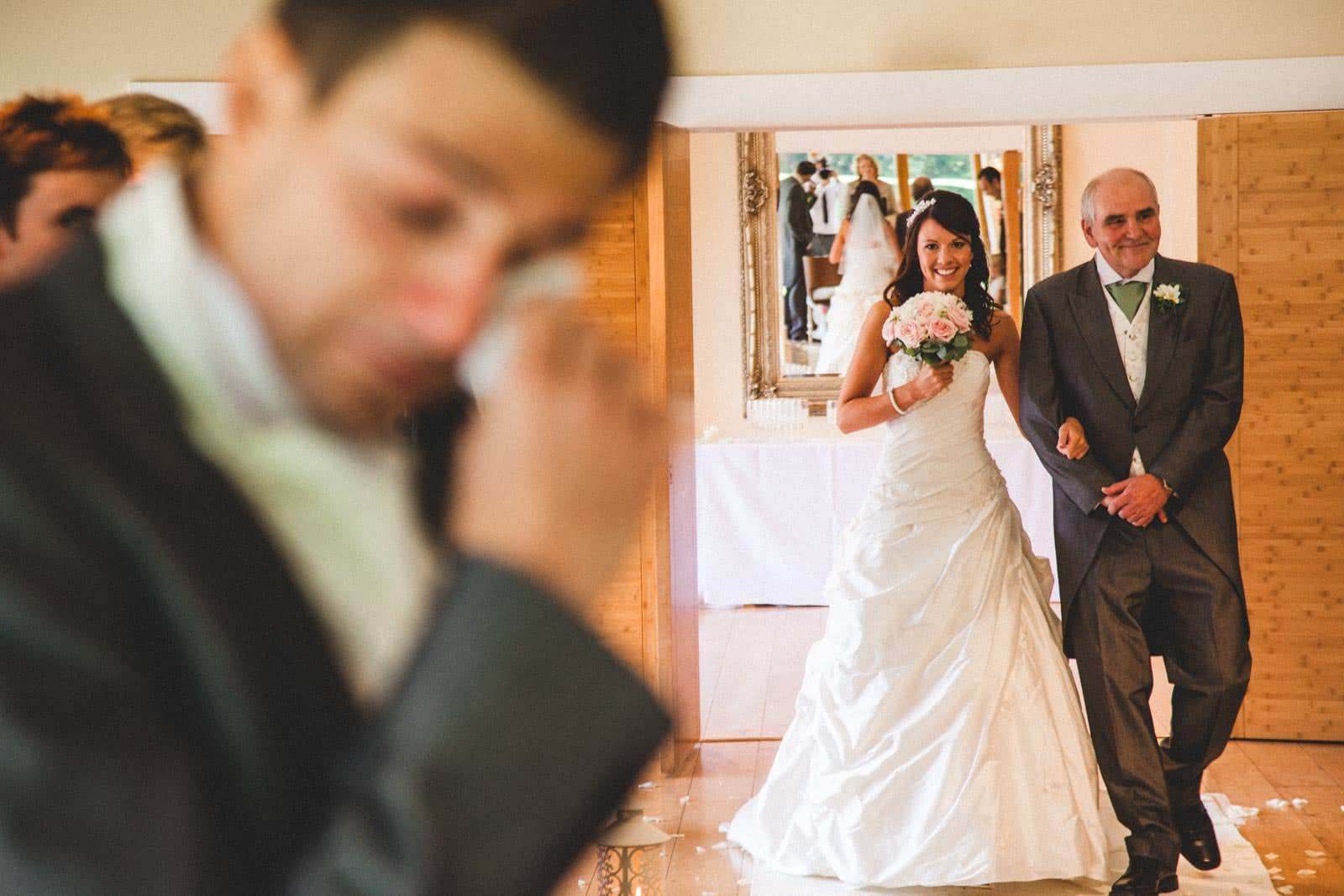 Groom crying in the foreground as Bride enters the room with her father