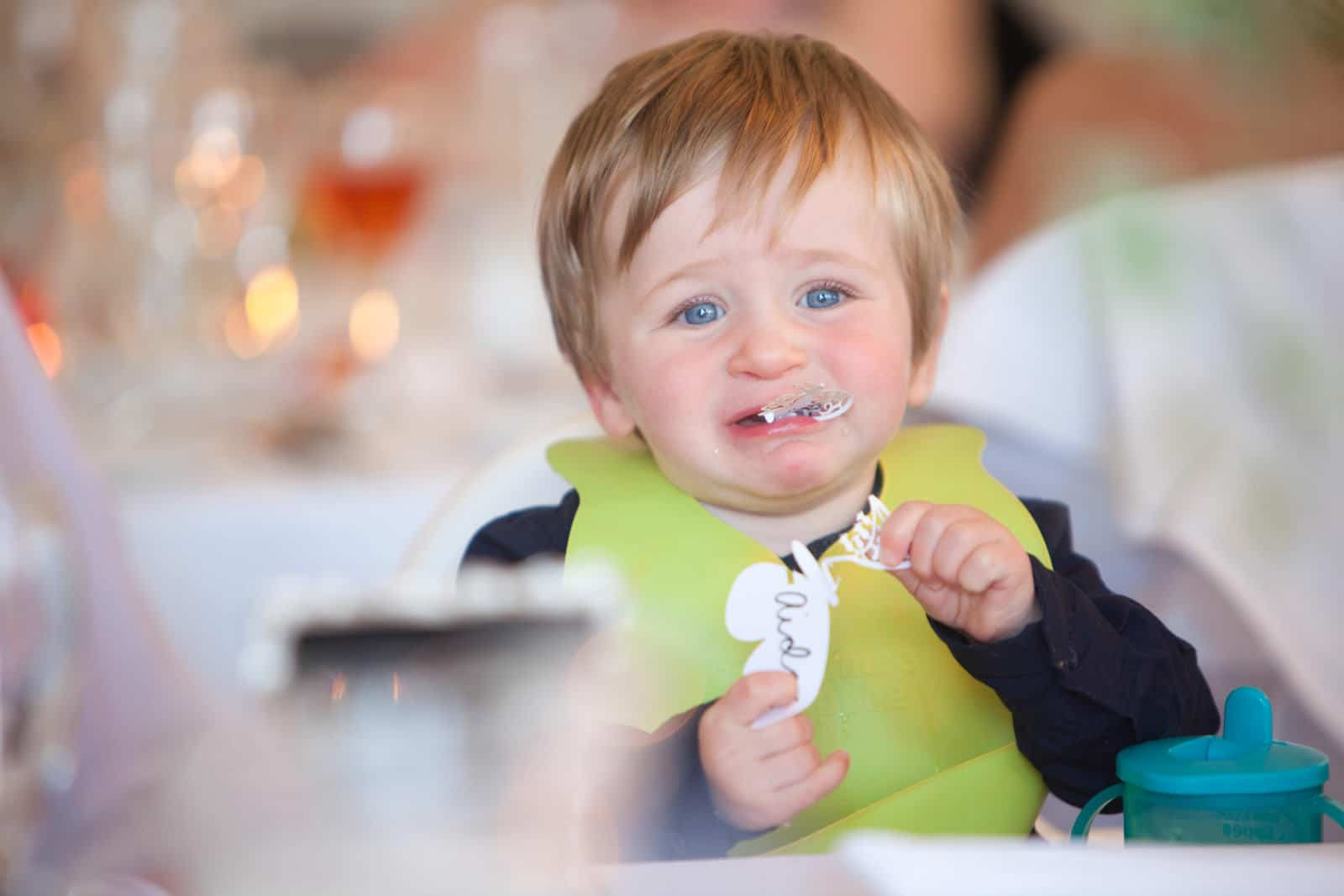 A child so hungry he is eating a paper wedding decoration