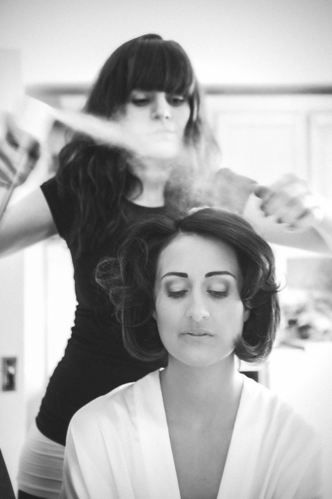 Hairspraying the brides hair in black and white