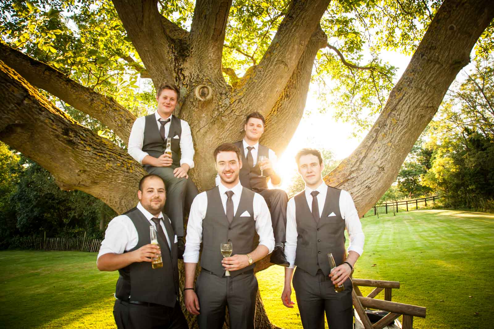 Groomsmen drinking beer in the tree at Crockwell Farm with the sun going down