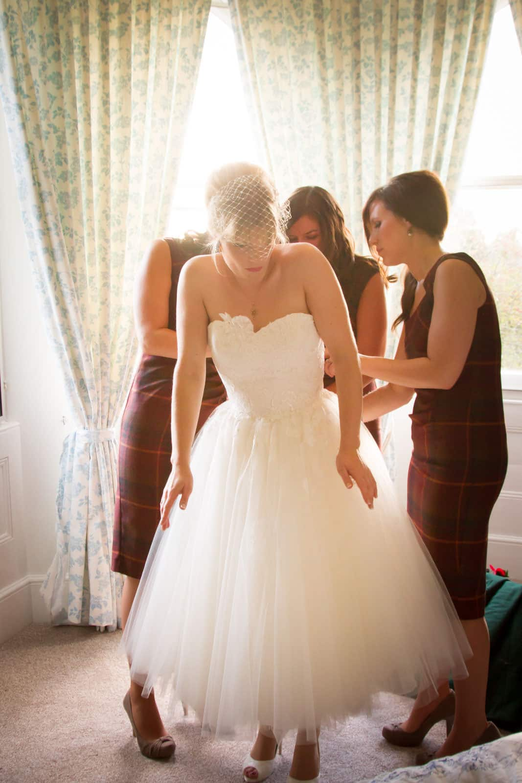 Bridesmaids doing up wedding dress for bride