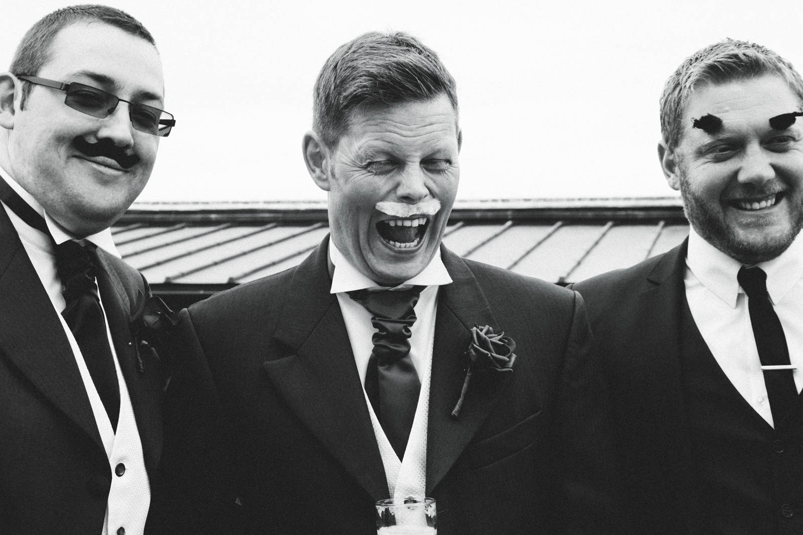 Funny Wedding photo of groomsmen messing around with moustaches