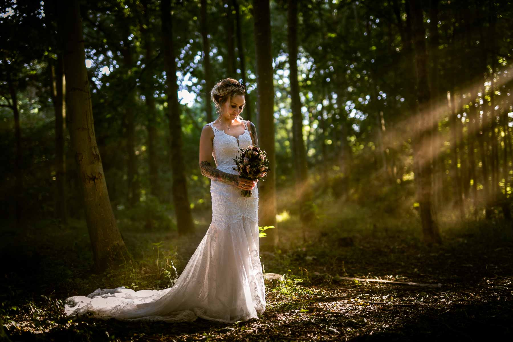 beautiful ethereal photo of a bride in a wood in east hunsbury country park, with sun beams piecing the woodland canopy