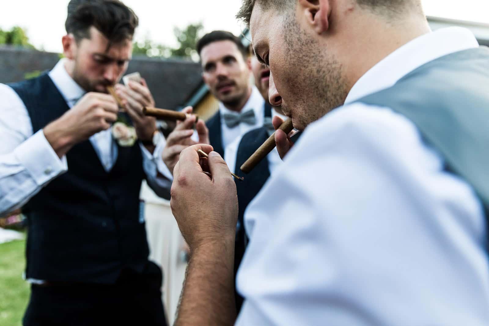 Groomsmen lighting cigars at a wedding at swallows nest barn