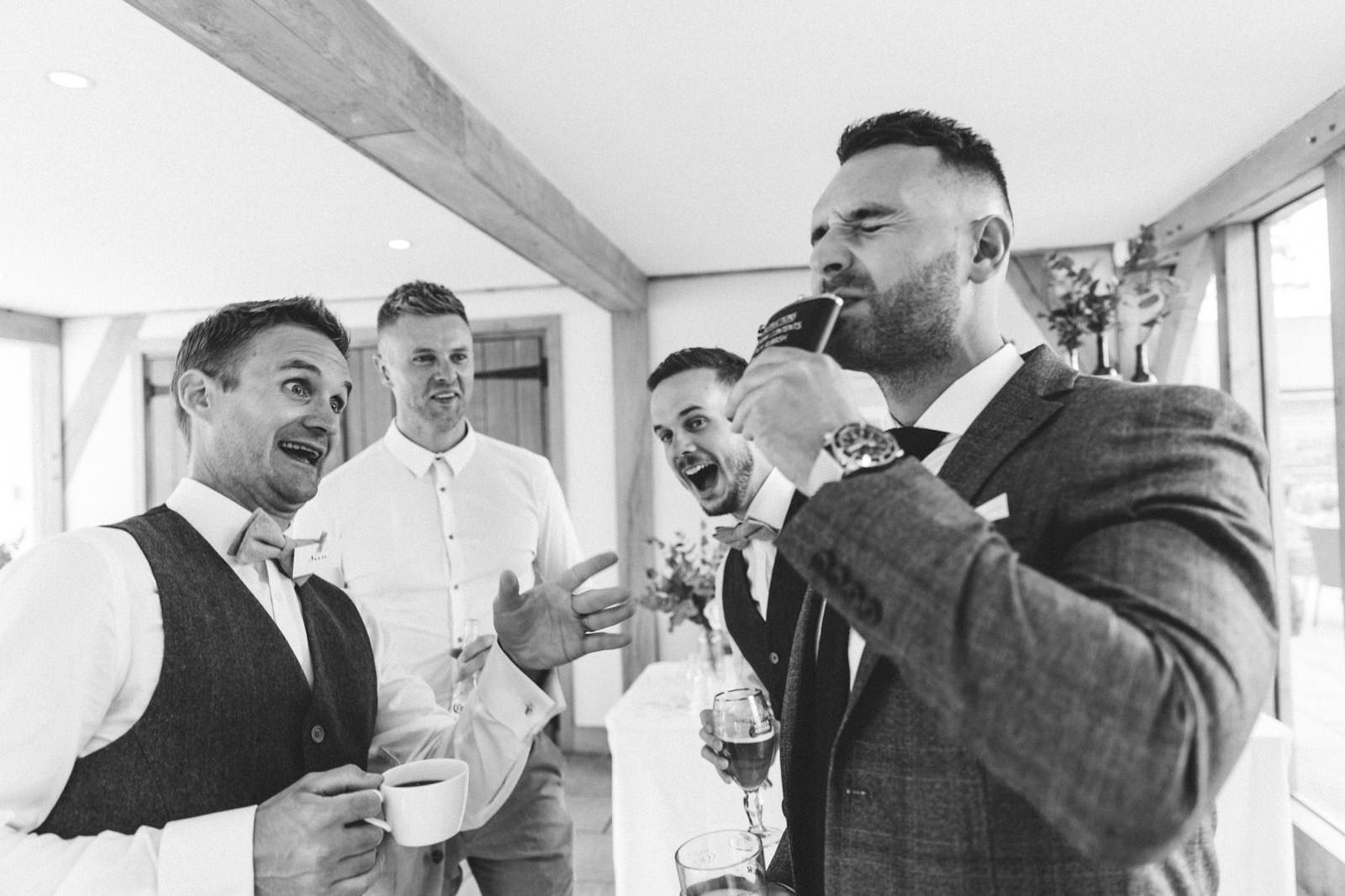 Wedding guest playing silly gaes and drinking a strong alcoholic drink