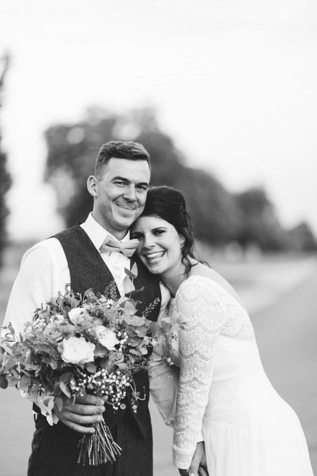 Newly married couple smiling at the camera at bassmead manor wedding venue