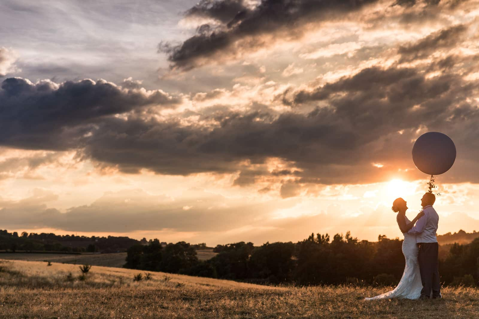 Silhouette of a bride and groom holding a balloon on their wedding day. Photo taken at Dodford Manor
