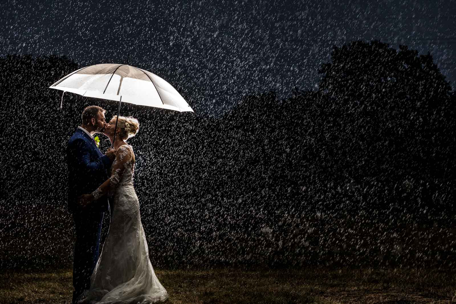 Couple kissing in the rain on their wedding day