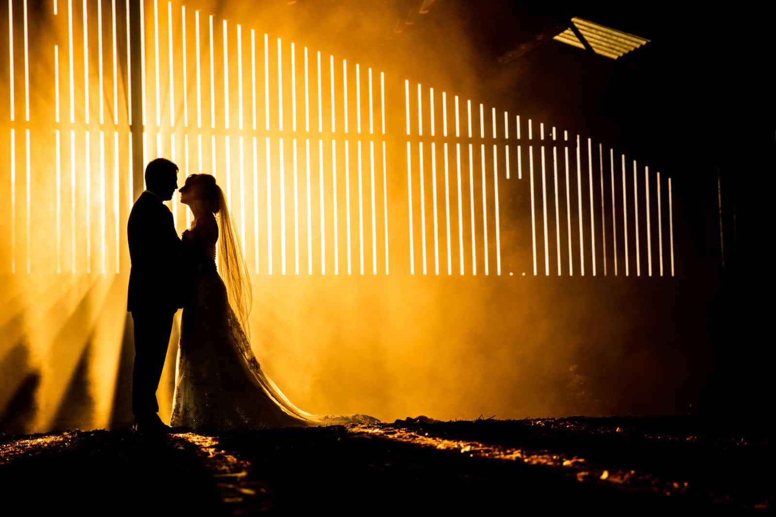 Silhouette of a couple kissing in a barn, using magmod, off camera flash and smoke grenade