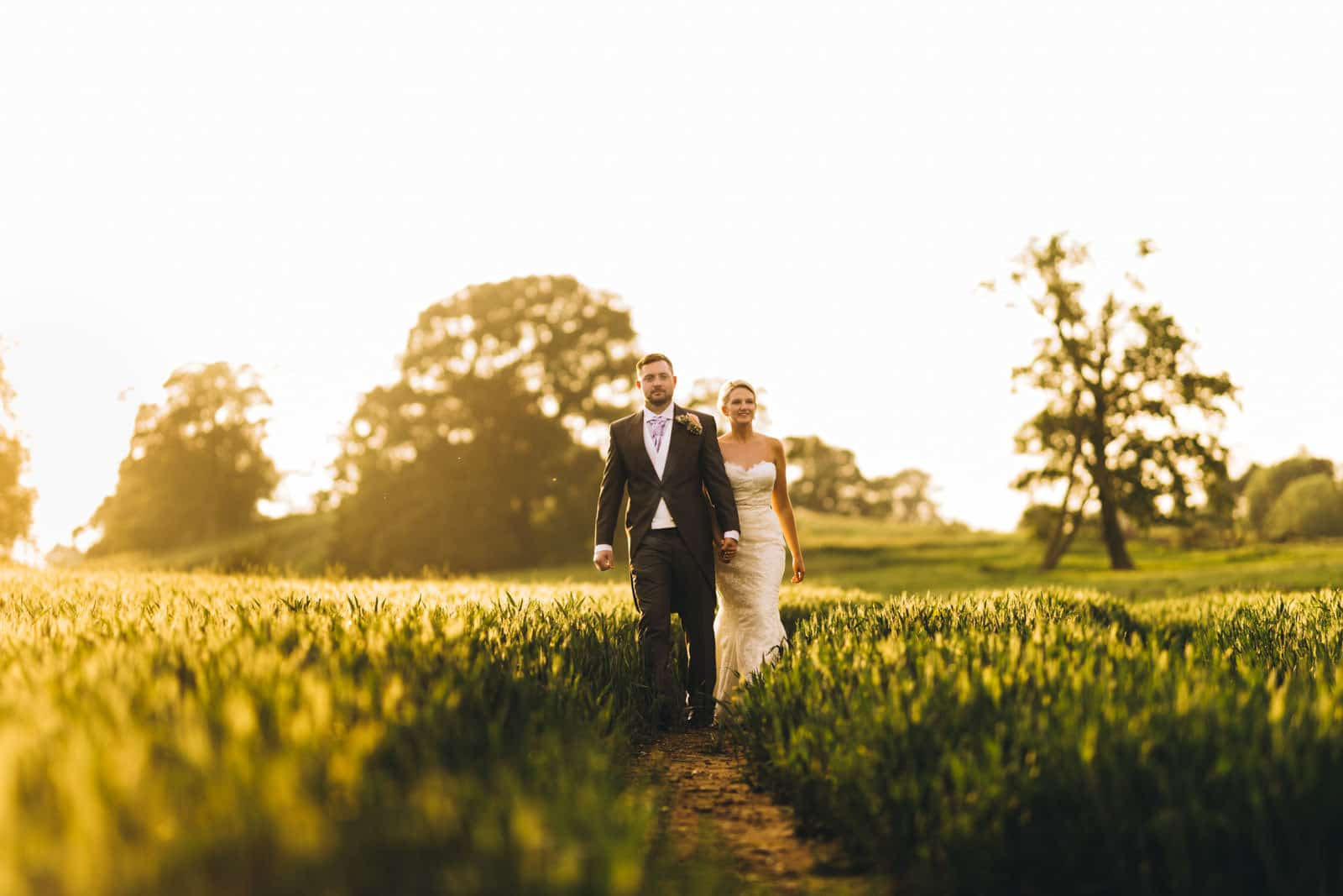 bride and groom walking in a wheat field in golden hour