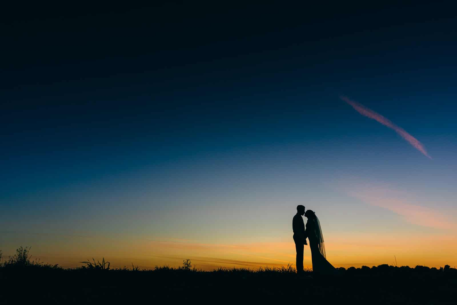 Gorgeous silhouette photo of bride and groom after sun down dusk