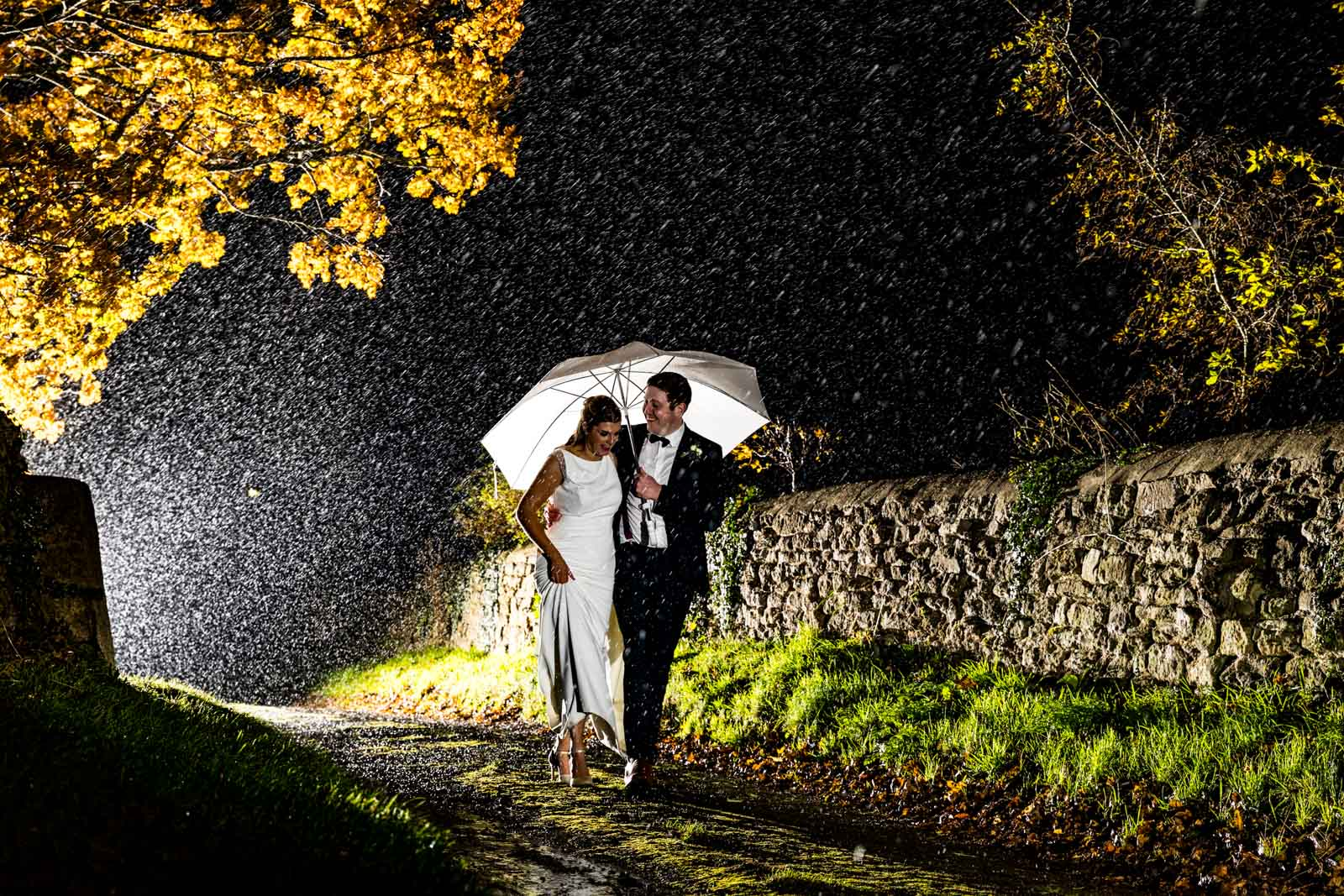 What happens if if rains on your wedding day photo of a bride and groom walking in the rain at Dodford Manor
