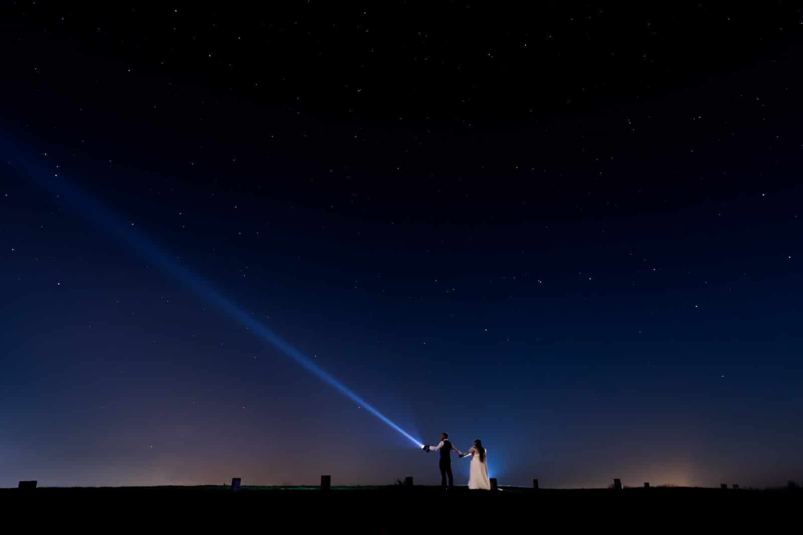 Winter Wedding at Dodford Manor, Creative photo of couple at night with stars and a torch