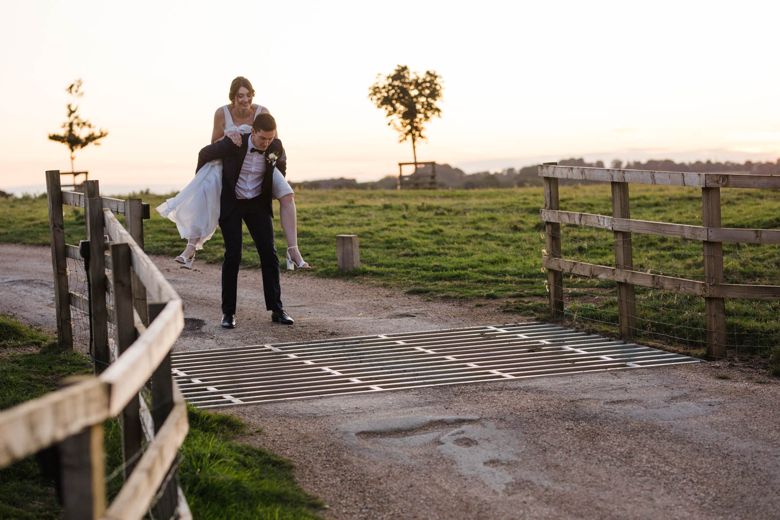 groom piggy backing his bride over cattle grid at dodford manor