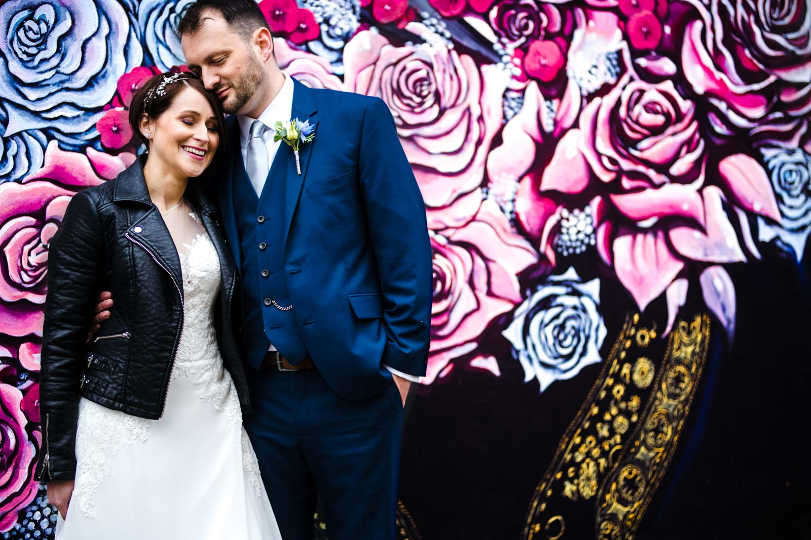 Bride and Groom standing in front of graffiti