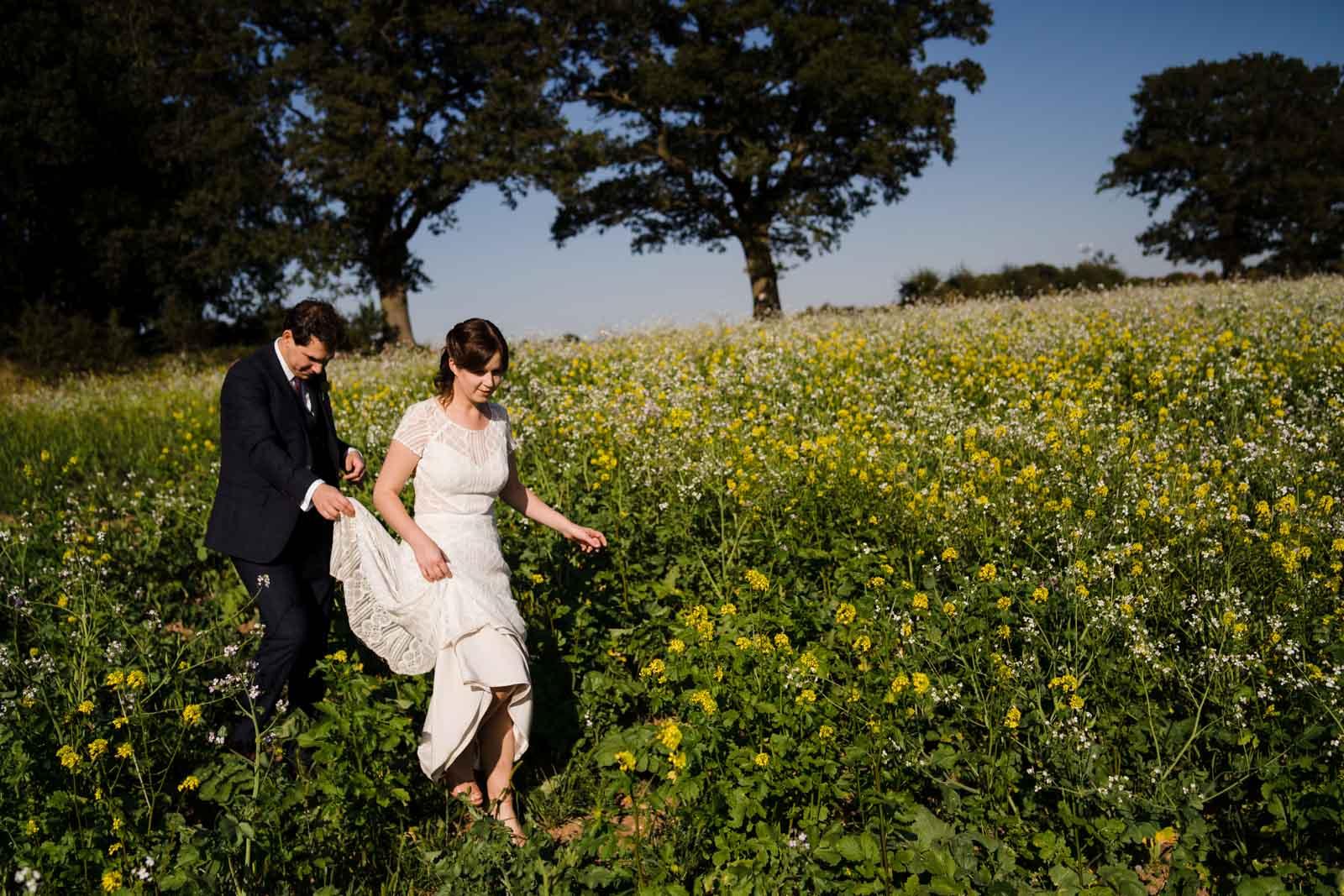 Bride and groom walking through the fields at swallows nest barn Wedding Photographer Warwickshire