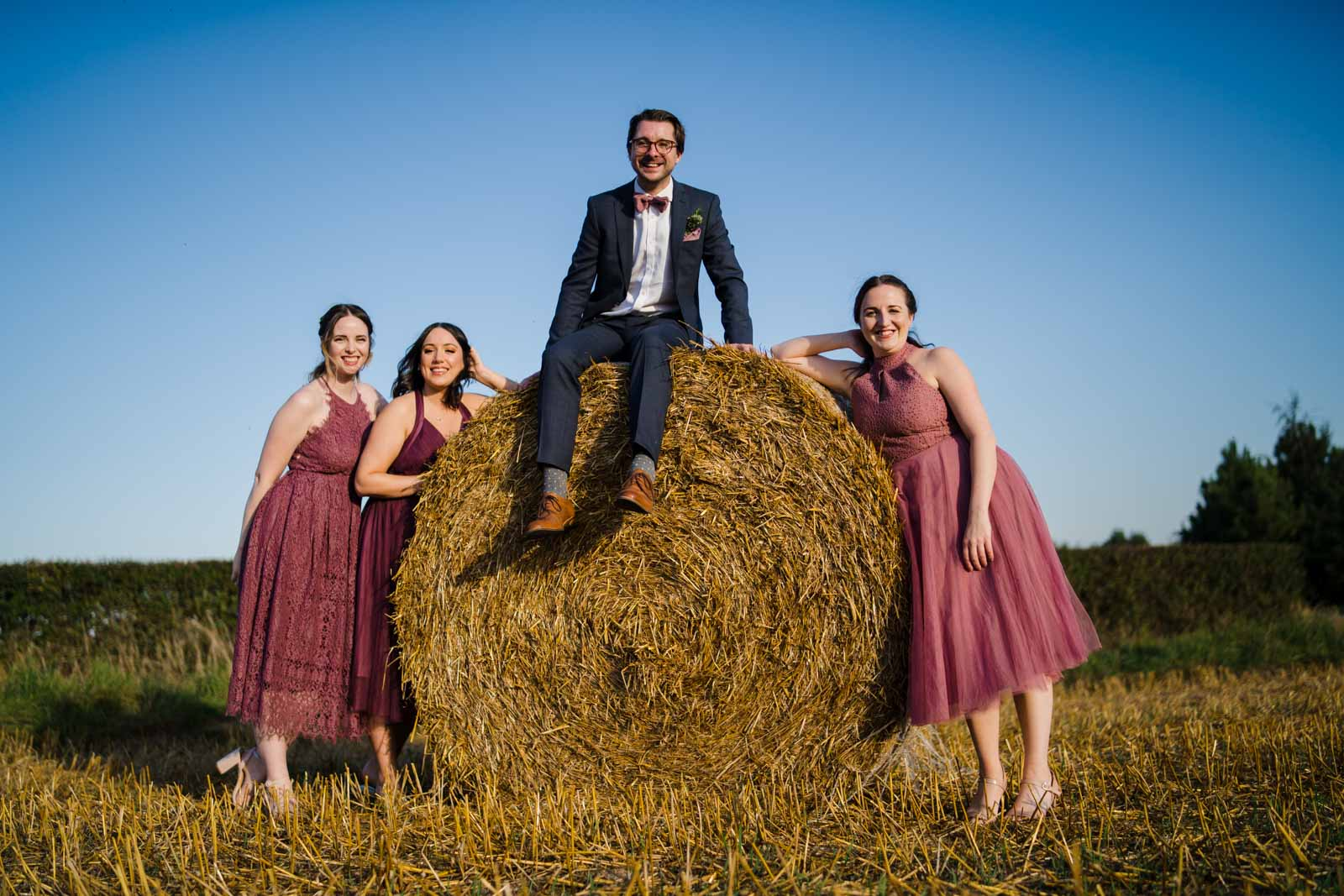 Guests sitting on a hay bale Wedding Photographer Warwickshire