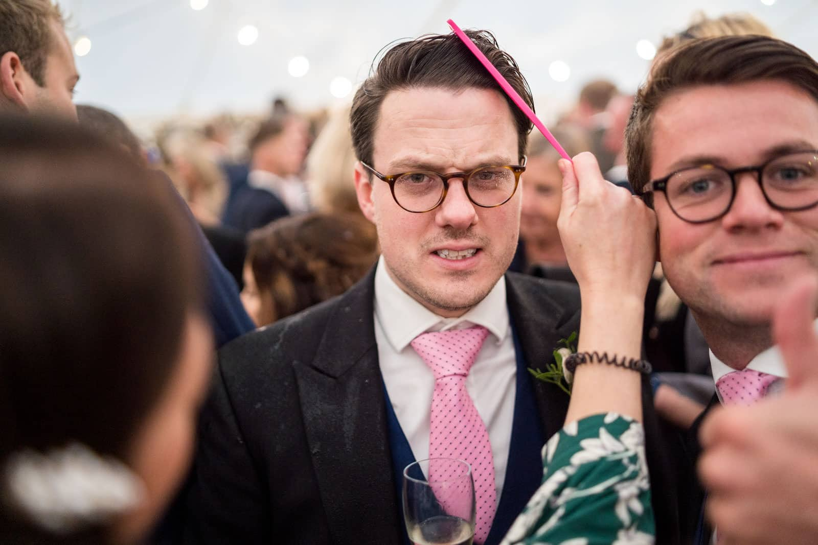 Awkward photo of a wedding guest having their hair combed by girlfriend