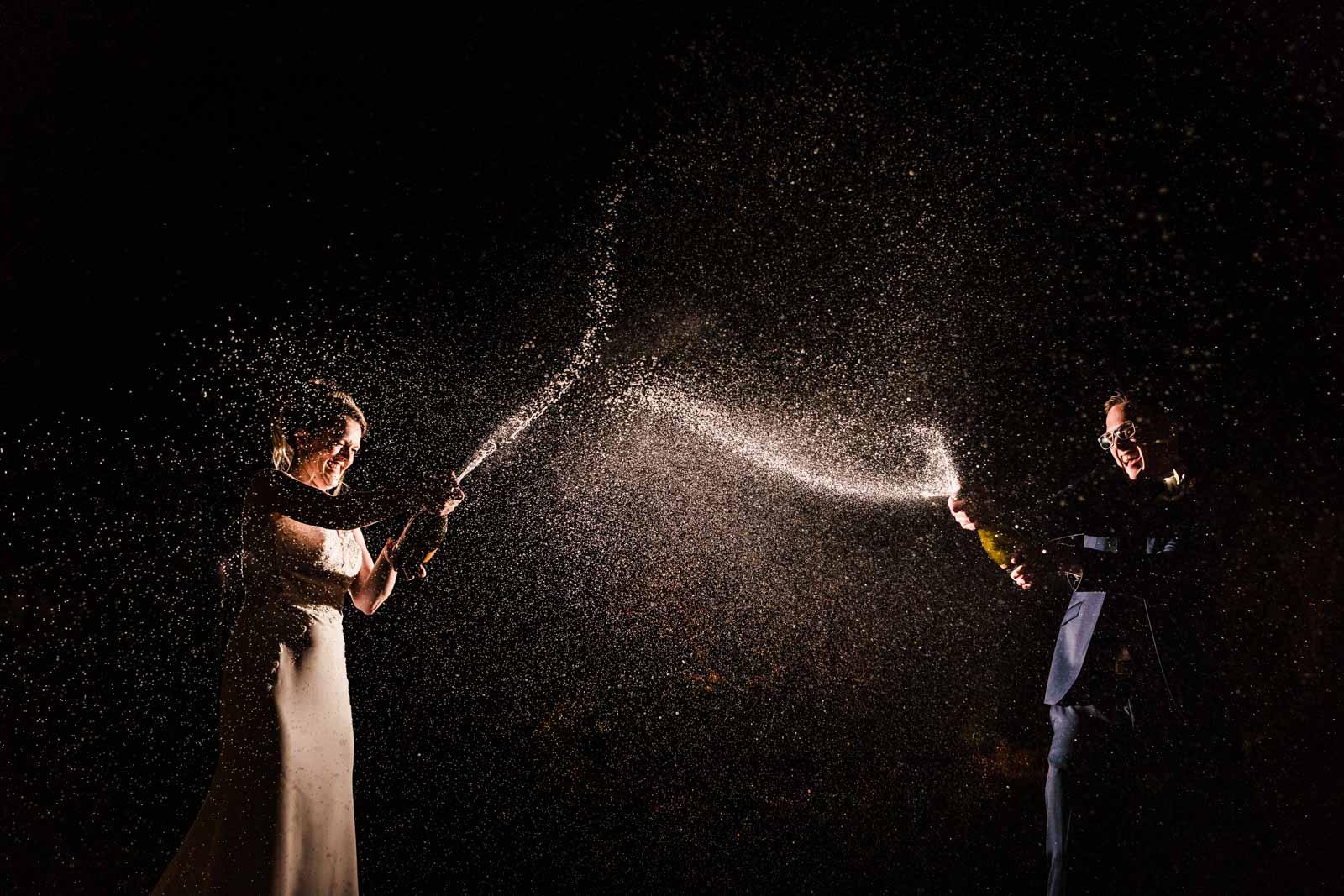 Champagne splash off camera flash photo of couple popping champagne bottle - creative wedding photography