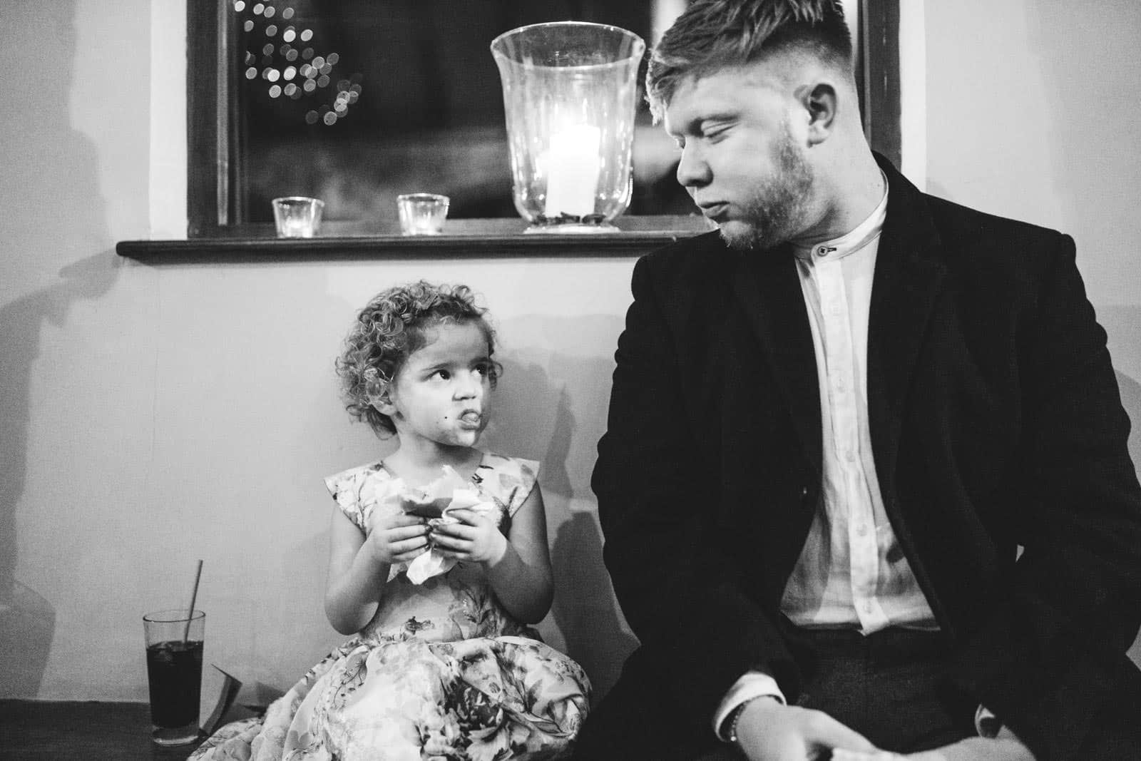 little girl looking at her dad whilst eating a burger at a wedding reception in Dodmoor house