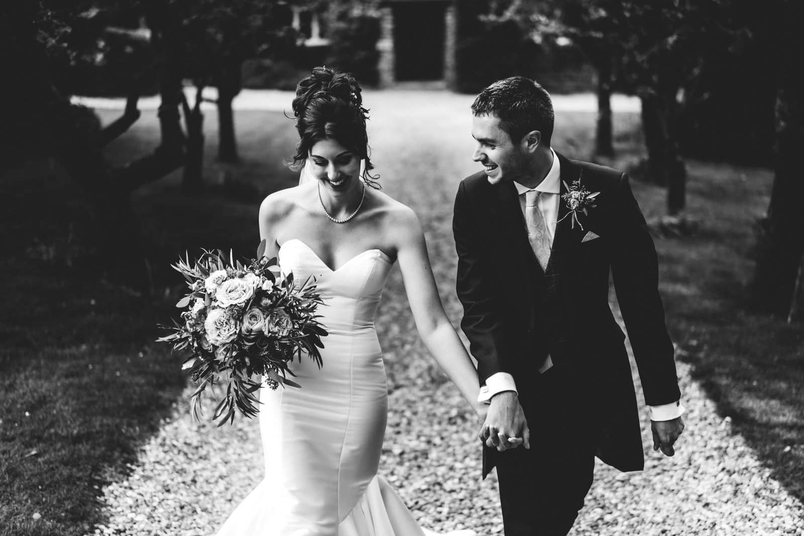Stunning photo of bride and groom walking together Cotswolds Wedding Photographers