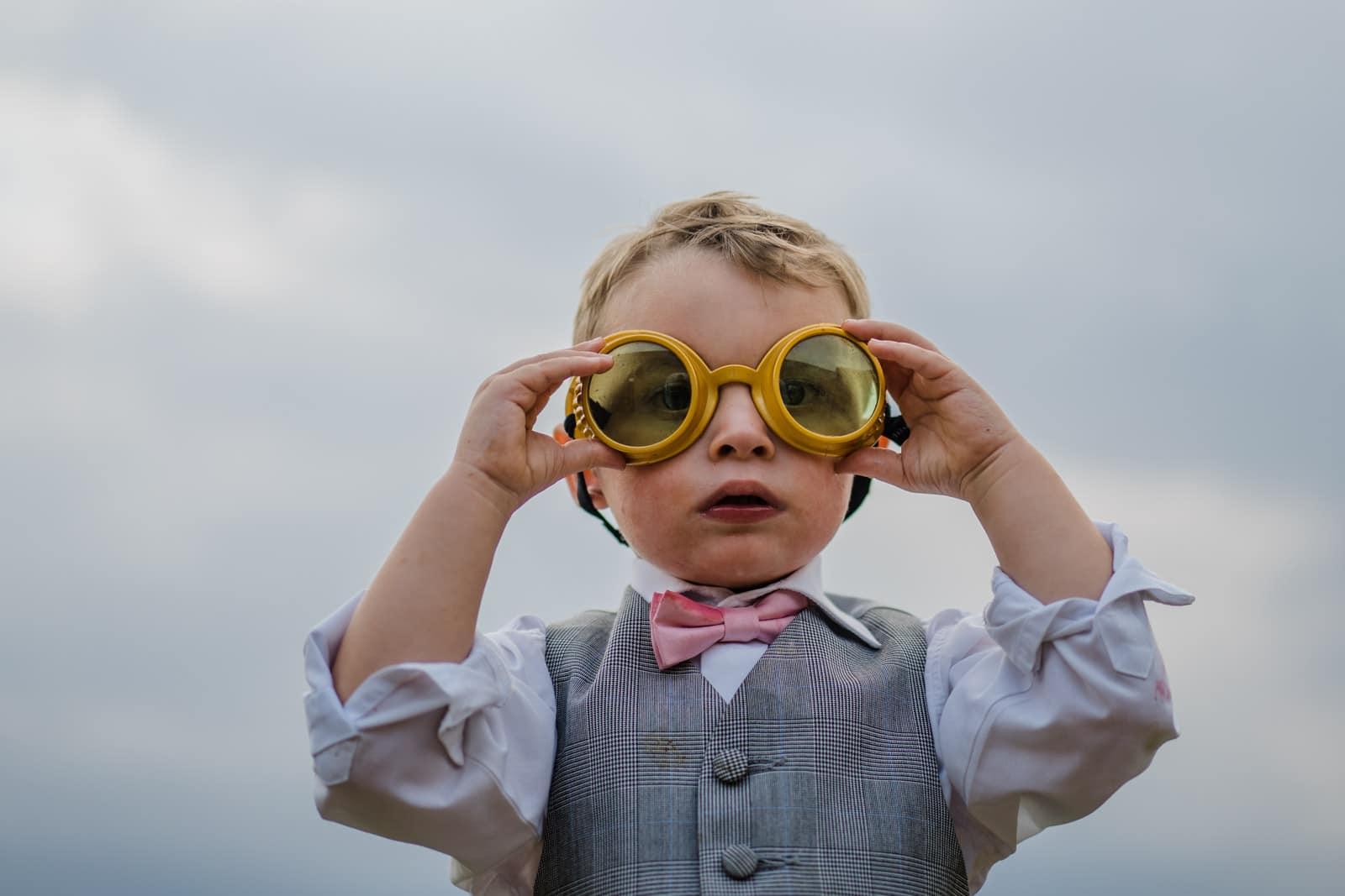 Wedding guest child adjusting his glasses