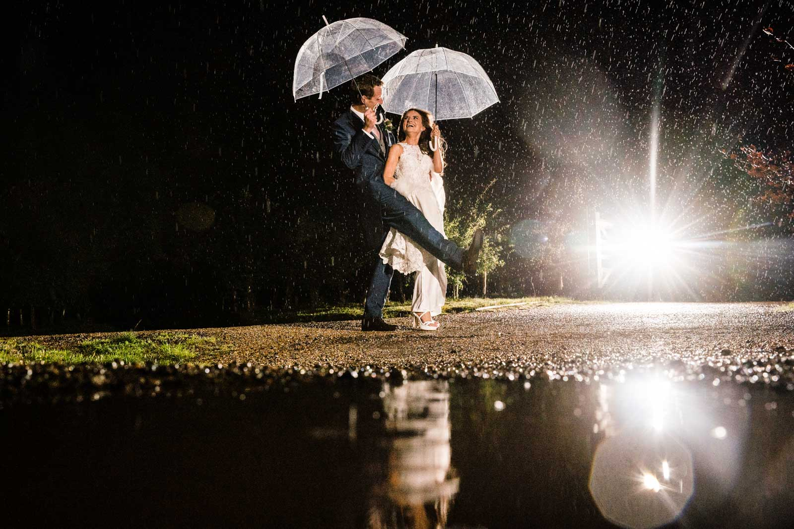 Dancing in the train photo of the wedding couple standing next to a puddle and dancing at night