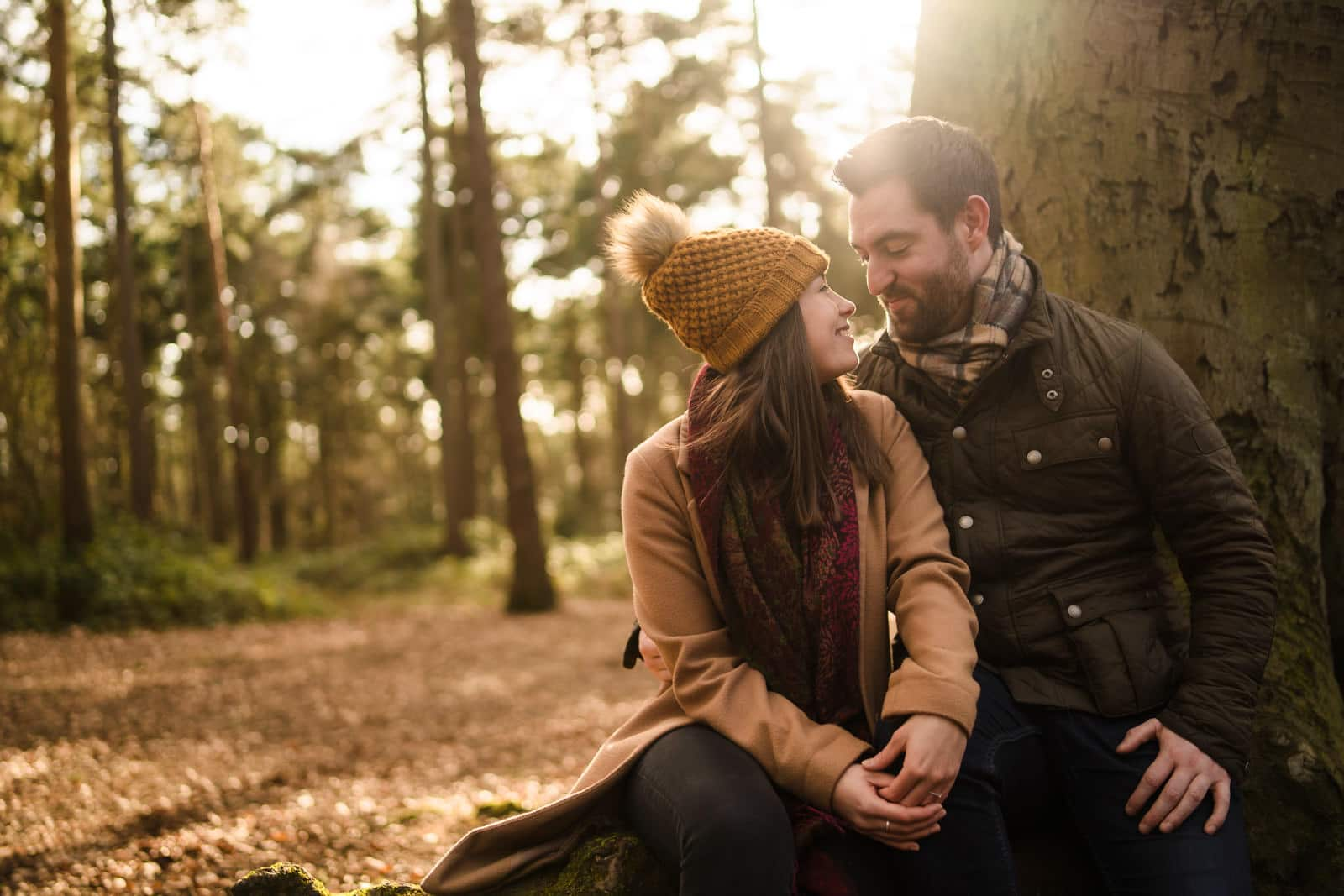 Couple sitting on tree logs at harleston firs