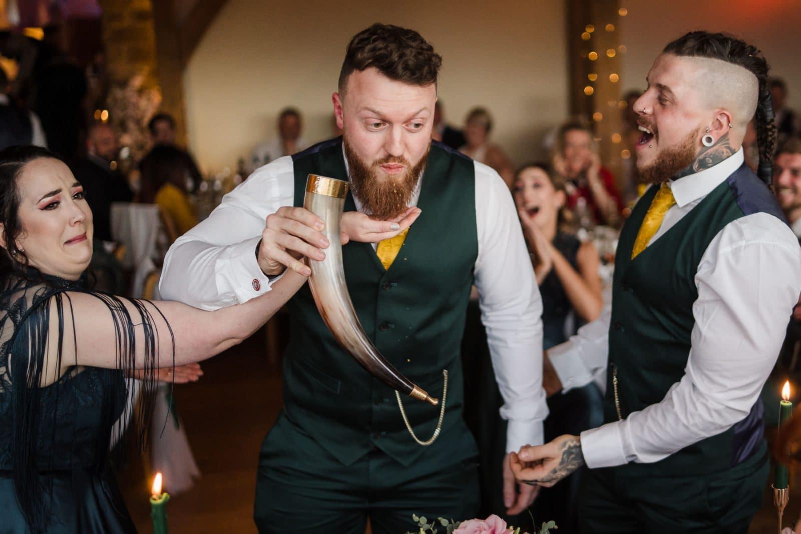 Groomsmen skolling a horn and spilling